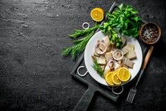 盐味的鲱鱼片断用草本、香料和柠檬 免版税库存图片