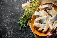盐味的鲱鱼片断用麝香草 库存图片