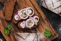 盐味的鲱鱼用黑麦面包和葱在土气黑暗的背景 在视图之上 库存图片