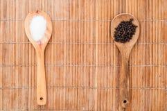 盐和胡椒在木匙子 免版税库存图片