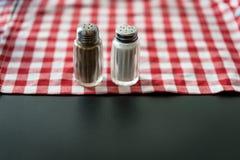 盐和胡椒在红色和白色格子花呢披肩洗碗巾 免版税库存照片