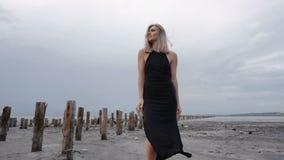 盐峡湾海岸的可爱的苗条金发碧眼的女人有健康黑泥的与木利益推出的形式地面 股票视频
