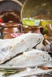 盐渍鳕鱼在厨房的桌上切开了 免版税库存照片