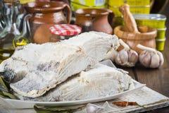盐渍鳕鱼在厨房的桌上切开了 免版税库存图片