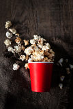 盐溶在一个红色纸板箱的玉米花在木桌上,戏院 库存照片