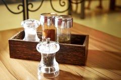 盐溶辣椒牛至和黑胡椒在桌上 免版税库存照片