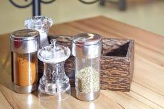 盐溶辣椒牛至和黑胡椒在桌上 库存图片