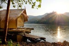 盐水湖的传统竹木筏房子有在khao越共水库Suphanburi省泰国的山背景 免版税库存图片