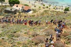 盐水湖6月9日, Balos,克利特,希腊 游人人群小山的对海盗堡垒 免版税库存图片