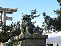 监护人在宫岛海岛,广岛,日本上的狮子雕象 免版税图库摄影