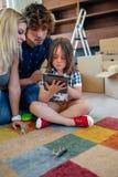 监督他们的小儿子的父母演奏片剂 免版税库存图片