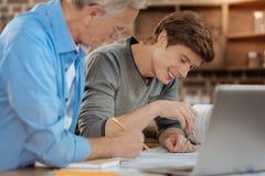 监督他的年轻同事图画图纸的资深辅导者工程师 库存图片