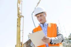 监督员文字低角度视图在剪贴板的在建造场所 免版税库存图片