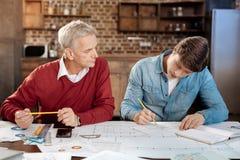 监督年轻同事图画图纸的老人 免版税库存照片