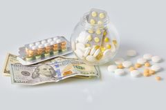 盒与三盒的医学药片硬币和有美元现金金钱的玻璃瓶 免版税库存照片
