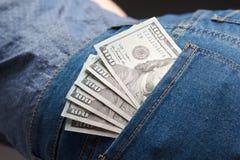 盒在妇女牛仔裤的美元钞票装在口袋里 免版税库存照片