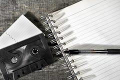 盒式磁带和空白的笔记本在桌上 库存图片