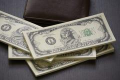 盒美国钞票和棕色皮革钱包 免版税图库摄影