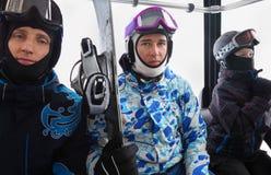 盔甲乘驾的三个滑雪者在缆索铁路 免版税库存图片