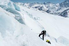 盔甲和滑雪帽的一名专业登山家在保险刻凹痕在冰川的冰斧 a工作  免版税图库摄影