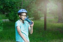 盔甲和绿色T恤杉骑自行车者的年轻男孩在公园喝从瓶的水 自行车的微笑的逗人喜爱的男孩在森林里 库存图片