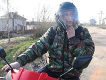 盔甲的一个人坐一辆红色摩托车 免版税图库摄影