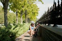 盔甲的体育女孩在驾驶前检查一辆自行车 库存照片