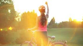 盔甲的女孩在自行车在有城市天际的公园 影视素材