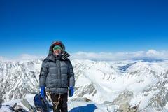 盔甲的妇女登山人和下来夹克用迁徙的棍子站立在山顶部 库存照片