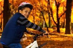 盔甲的男孩在自行车 库存照片