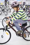 盔甲的男孩坐自行车并且查找得下来 免版税库存照片