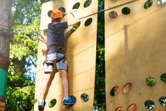 盔甲的逗人喜爱的年轻男孩用上升的设备在绳索游乐场 夏令营,假日 免版税库存照片