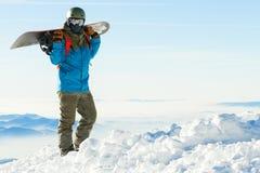 盔甲的年轻挡雪板在一座多雪的山的上面与美丽的天空的在背景 免版税库存照片