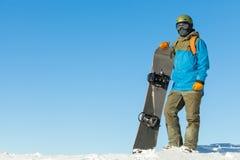 盔甲的年轻挡雪板在一座山的上面与美丽的天空的在背景 免版税库存图片