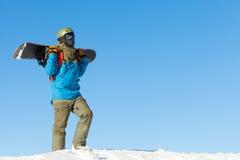 盔甲的年轻挡雪板散步在与美丽的天空的一座山顶部的在背景 免版税图库摄影