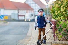 盔甲骑马的小孩男孩与他的滑行车在城市 免版税库存图片