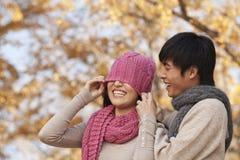 盖一个少妇的眼睛的年轻人用帽子 免版税库存图片