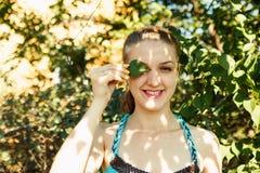 盖一只眼睛的俏丽的女孩由绿色叶子 免版税库存照片