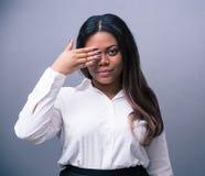 盖一只眼睛的非洲女实业家用手 库存照片