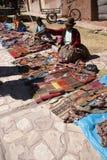 盖丘亚族人的印地安妇女出售五颜六色的手工制造毯子 库存照片