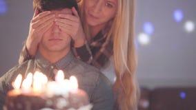 盖人的眼睛的白肤金发的女孩,然后让他看与许多蜡烛的蛋糕 人有生日庆祝 股票视频