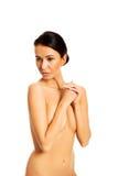 盖她的乳房的俏丽的被晒黑的妇女 库存照片