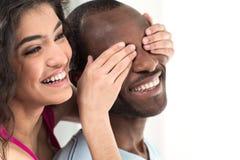 盖她的男朋友的女孩注视用两只手 免版税库存图片