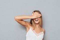 盖她的眼睛的一个愉快的女性少年的画象 免版税库存照片
