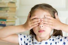 盖她的眼睛的小女孩用手 免版税库存照片