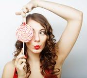 盖她的眼睛的微笑的逗人喜爱的女孩用在白色后面的棒棒糖 免版税库存图片