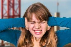 盖她的耳朵的妇女保护免受喧闹声 免版税库存照片