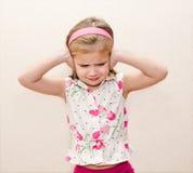 盖她的耳朵的小女孩 免版税库存图片