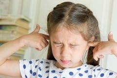 盖她的耳朵的小女孩 库存照片