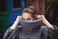 盖她的面孔的一件被编织的高领衫毛线衣的少妇 关闭 库存图片